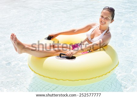 Full length portrait of happy young woman relaxing on inner tube in swimming pool - stock photo