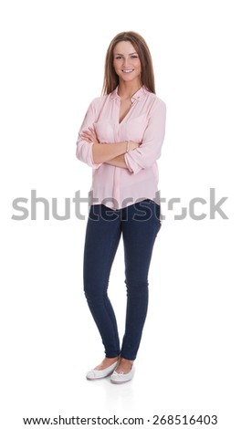 Full length portrait of happy young woman standing arms crossed over white background - stock photo