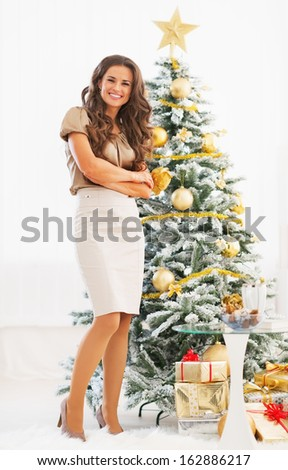 Full length portrait of happy young woman standing in front of christmas tree - stock photo