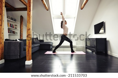 Full length portrait of healthy young lady going yoga workout at home. Fitness model exercising in living room. - stock photo