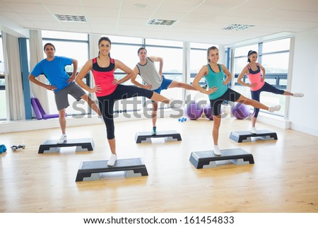 Full length portrait of instructor with fitness class performing step aerobics exercise in gym - stock photo