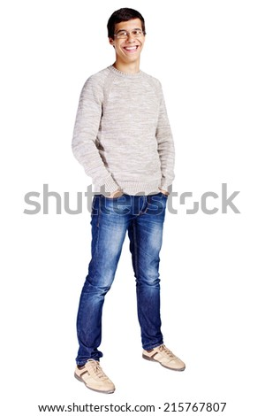 Full length portrait of laughing young man in glasses and beige sweater with hands in his jeans pockets isolated on white background  - stock photo