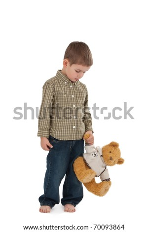 Full length portrait of little boy in jeans with toy bear on white background - stock photo