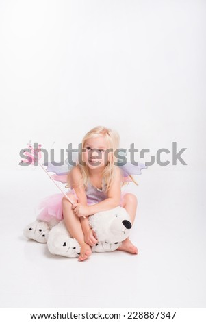 Full-length portrait of little fair-haired lovely girl wearing pretty grey vest and pink skirt sitting on the big teddy bear holding a magic wand. Isolated on white background - stock photo