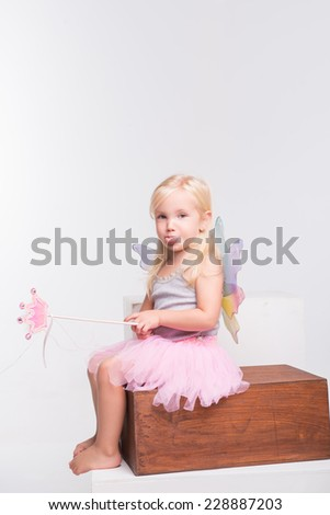Full-length portrait of little fair-haired lovely smiling girl wearing pretty grey vest pink skirt and white wings holding a magic wand sitting on the wooden chair showing us her tongue. Isolated on - stock photo