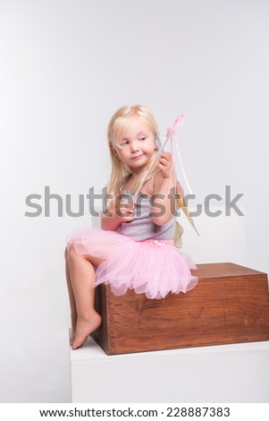 Full-length portrait of little fair-haired lovely smiling girl wearing pretty grey vest pink skirt and white wings holding a magic wand sitting on the wooden chairlooking for someone. Isolated on - stock photo