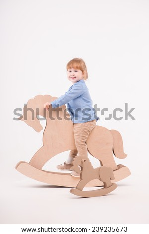 Full-length portrait of little lovely girl wearing blue shirt and brown pants rocking on the wooden toy horse near the little one. Isolated on the white background - stock photo