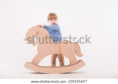 Full-length portrait of little lovely girl wearing blue shirt and brown pants standing near the wooden toy horse. Isolated on the white background - stock photo