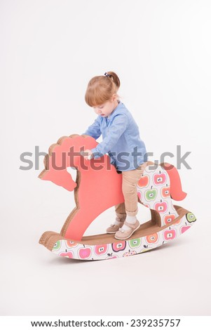 Full-length portrait of little lovely smiling girl wearing blue shirt and brown pants rocking on the pink wooden toy horse. Isolated on the white background - stock photo