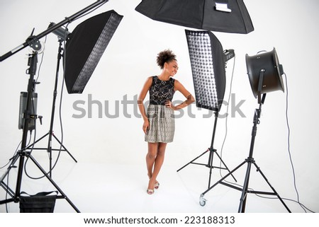 Full-length portrait of lovely African model wearing wonderful evening dress standing in front of projectors looking at someone - stock photo