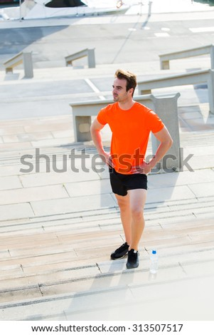 Full length portrait of male jogger dressed in bright copy space t-shirt taking break after workout outdoors, handsome man athlete with good sports build resting after an active run - stock photo