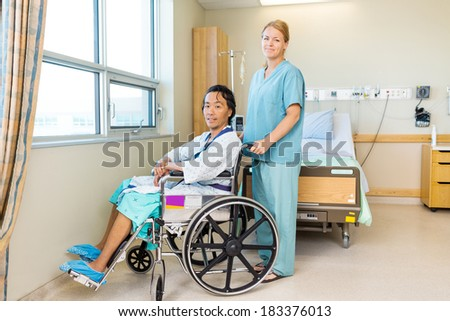 Full length portrait of male patient sitting on wheel chair while nurse standing behind at window in hospital - stock photo