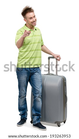 Full-length portrait of man with silver suitcase pointing at something with forefinger, isolated on white. Concept of traveling and cool vacations - stock photo