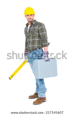 Full length portrait of manual worker with spirit level and toolbox on white background - stock photo