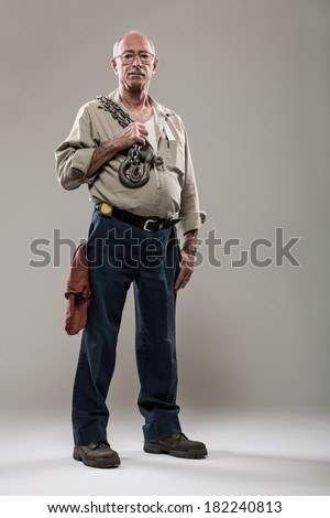 Full Length Portrait of Mechanic with an Industrial Chain and Hook - stock photo