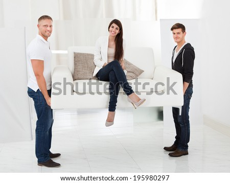 Full length portrait of movers carrying sofa with happy client woman sitting - stock photo