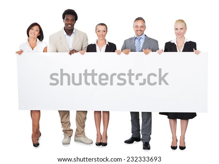 Full length portrait of multiethnic business people holding large billboard over white background - stock photo