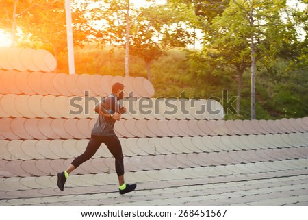 Full length portrait of muscular build sports man running along beautiful wall outdoors, male runner working out outside at amazing sunset light, filtered image, flare sunset light - stock photo