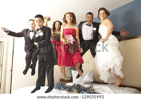 Full length portrait of newly wedded couple with bridesmaids and groomsmen jumping on bed. Horizontal shot. - stock photo