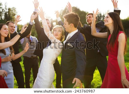 Full length portrait of newlywed couple dancing and having fun with bridesmaids and groomsmen in green sunny park - stock photo