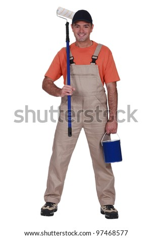 full-length portrait of painter holding tin of paint and roller - stock photo