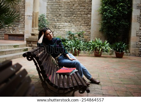 Full length portrait of pensive brunette hair woman sitting in beautiful spanish patio bench propping up her head with hands and look to the camera - stock photo