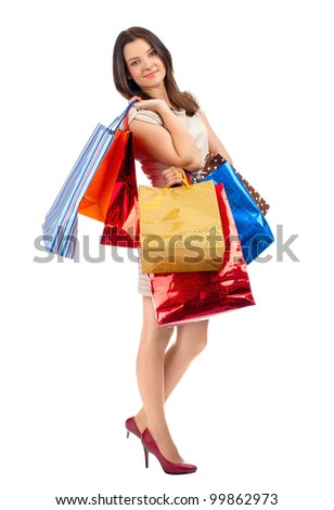 Full length portrait of pretty young woman with colorful shopping bags. Isolated on white background - stock photo