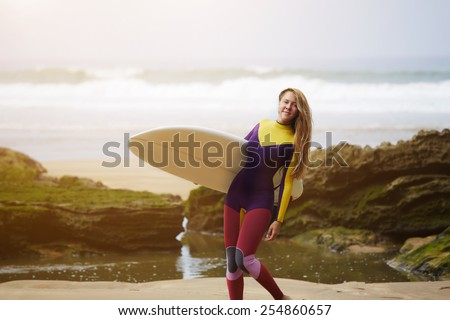 Full length portrait of professional female surfer holding her surfboard smiling, sexy surfer girt standing against ocean with beautiful waves on background, cross process image, flare sun light - stock photo