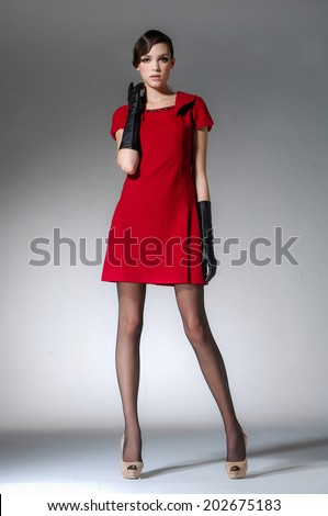full-length portrait of professional model in red dress on light background  - stock photo