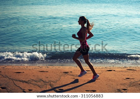 Full length portrait of purposeful woman runner with beautiful figure doing daily evening run on the beach,young female athlete with hair tied up in a ponytail engaged in active sports against the sea - stock photo