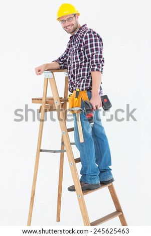 Full length portrait of repairman climbing ladder while holding power drill on white background - stock photo