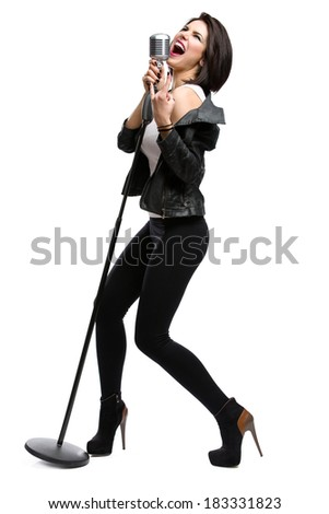 Full-length portrait of rock singer wearing leather jacket and keeping static microphone, isolated on white. Concept of rock music and rave - stock photo
