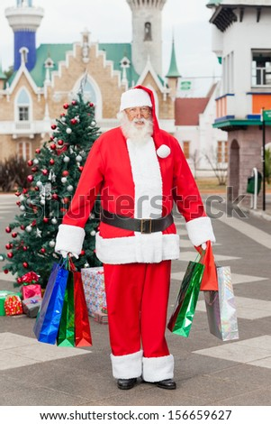 Full length portrait of Santa Claus carrying shopping bags in courtyard - stock photo