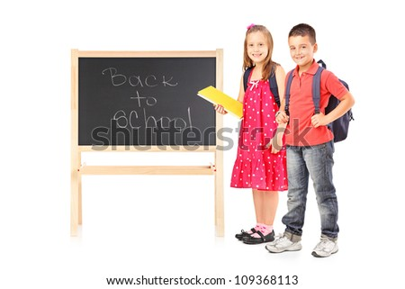 Full length portrait of schoolgirl and boy posing next to a board isolated on white background - stock photo