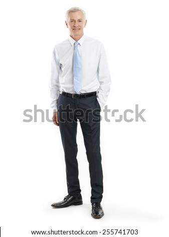 Full length portrait of senior businessman standing against white background. - stock photo