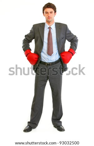Full length portrait of serious modern businessman in boxing gloves - stock photo