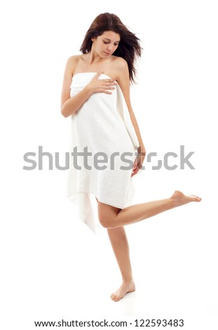 Full length portrait of sexy beautiful young woman wrapped in towel with long healthy hair isolated over white background.  Concept of natural beauty care skin, legs, spa bath - stock photo