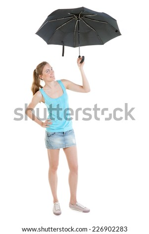 Full-length portrait of sexy lass wearing jeans mini-skirt, blue t-shirt and gumshoes with black umbrella - stock photo