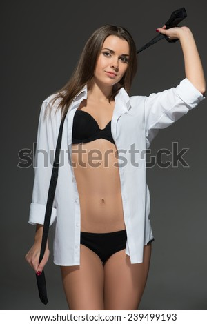 Full-length portrait of sexy young Caucasian brunette wearing men white shirt with tie undone, sensual provocative look - stock photo