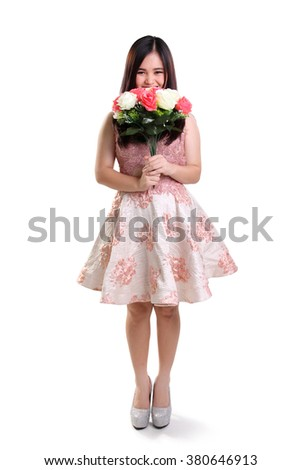 Full length portrait of shy teenage girl smiling and covering her face with flowers, isolated on white background - stock photo