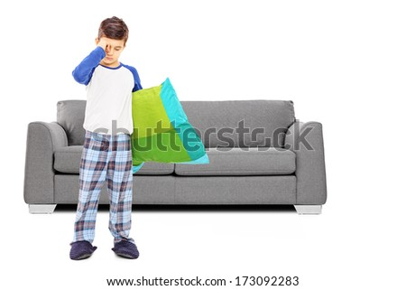 Full length portrait of sleepy boy in pajamas standing in front of sofa isolated on white background - stock photo