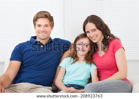 Full length portrait of smiling family sitting on sofa at home - stock photo