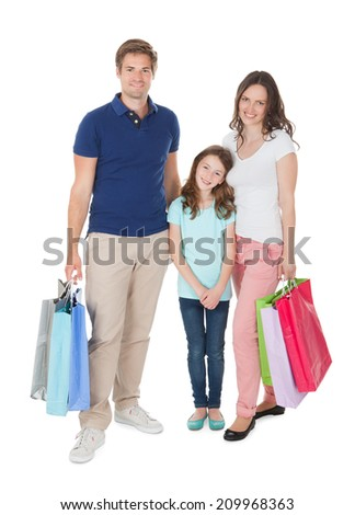 Full length portrait of smiling family with shopping bags standing over white background - stock photo