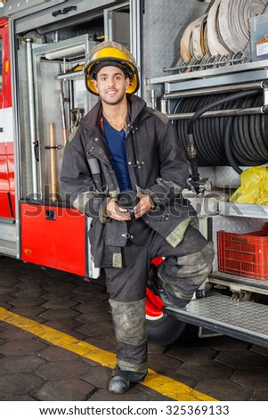 Full length portrait of smiling fireman holding coffee mug while standing by truck at fire station - stock photo