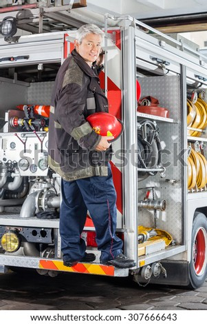 Full length portrait of smiling fireman standing on truck at fire station - stock photo