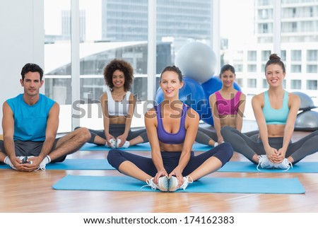Full length portrait of smiling fit class doing the butterfly stretch in exercise room - stock photo