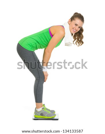 Full length portrait of smiling fitness young woman weighing on scales - stock photo