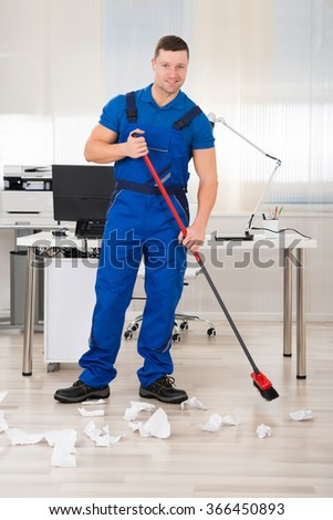 Full length portrait of smiling janitor holding broom while standing in office - stock photo