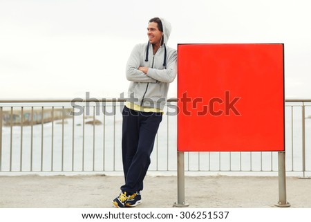 Full length portrait of smiling male jogger taking break after an active run outdoors while standing near a red board with copy space area for text message or content,sportsman resting after training - stock photo