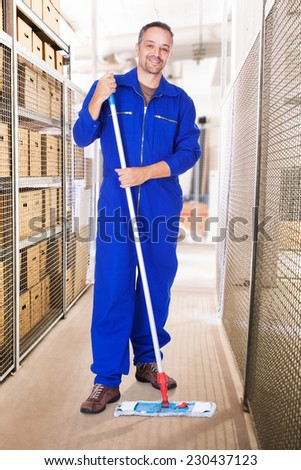 Full length portrait of smiling male worker cleaning warehouse with mop - stock photo